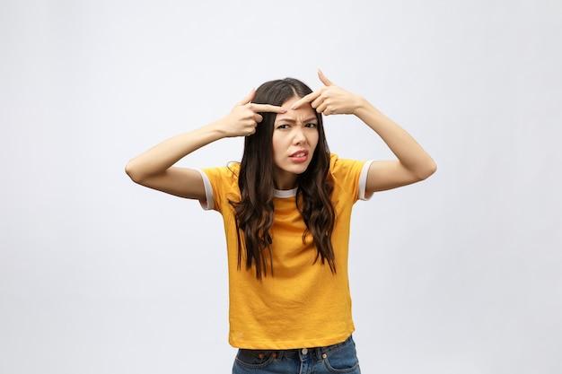 Problem skóry twarzy - młoda kobieta nieszczęśliwa dotyka jej skóry na białym tle, koncepcja pielęgnacji skóry