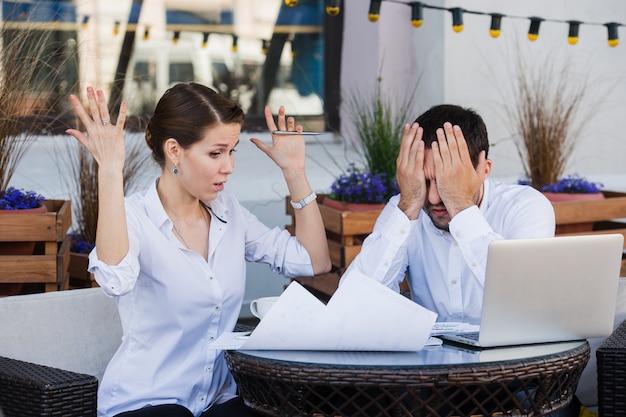 Problem z działaniem konfliktu ludzi biznesu, zły szef argumentuje krzyczeć do kolegi biznesmenów i poważnych argumentów negatywnych emocji omawiając raport w kawiarni na świeżym powietrzu podczas przerwy na lunch
