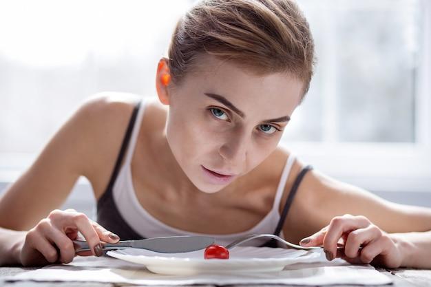 Problem z wagą. blada kobieta z niedowagą krojąca pomidora z problemem wagi