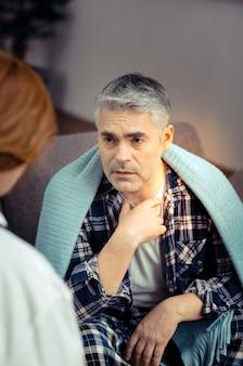 Problem zdrowotny. przyjemny, przystojny mężczyzna rozmawiający ze swoim lekarzem, skarżący się na ból gardła