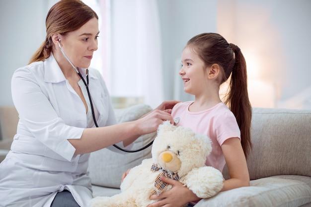 Problem zdrowotny. wesoła miła dziewczyna siedzi na kanapie i przytulanie pluszowego misia, podczas gdy kobieta lekarz za pomocą stetoskopu