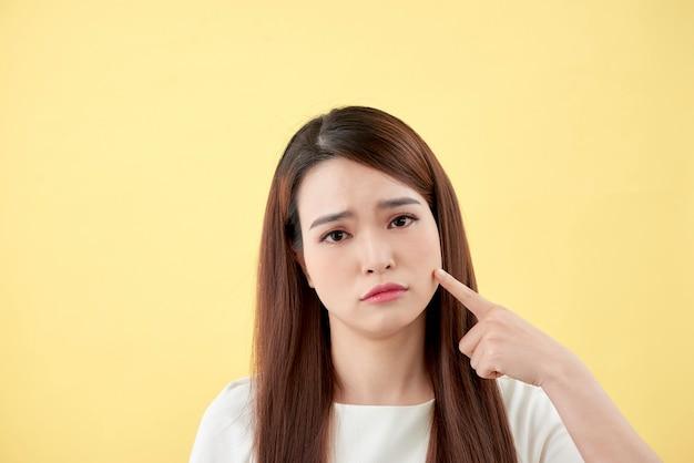 Problem ze skórą twarzy - młoda kobieta nieszczęśliwa dotyka jej izolowanej skóry, koncepcja pielęgnacji skóry, azjatka
