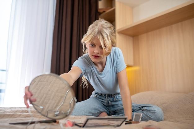 Problemy skórne. dziewczyna w niebieskiej koszuli siedząca na łóżku i patrząca w lustro znajdująca alfonsów