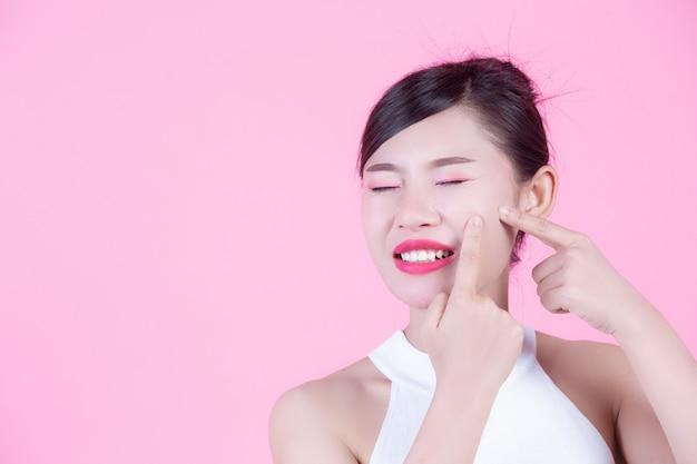 Problemy skóry twarzy kobiety - nieszczęśliwe młode kobiety dotyka jej skórę na różowym tle.