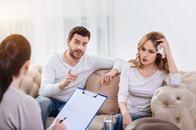 Problemy w relacjach. miły, ponury młody mężczyzna siedzi obok żony i podczas sesji psychologicznej opowiada psychologowi o swoim problemie rodzinnym