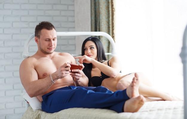 Problemy w rodzinie. zła młoda kobieta leżąca na łóżku przeciwko mężowi, który gra przez telefon.