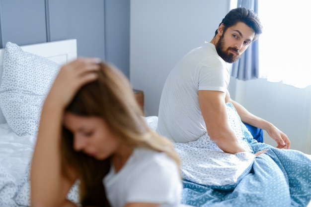 Problemy w związkach. młoda para siedzi w sypialni i walczy. oboje wyglądali na smutnych i rozczarowanych.