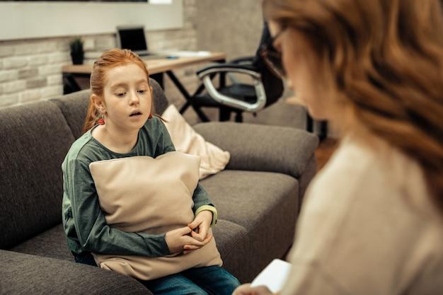 Problemy z dzieciństwa. smutna, smutna dziewczyna opowiadająca o swoich trudnościach życiowych podczas sesji z psychologiem