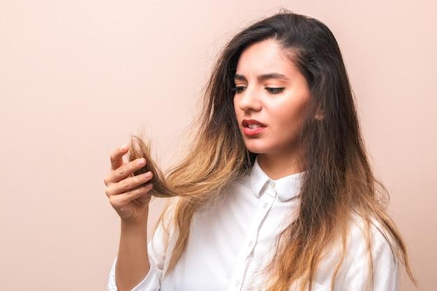 Problemy z włosami młoda kobieta w białej koszuli, sprawdzając jej zarost, uszkodzone i podzielone włosy na różowym tle