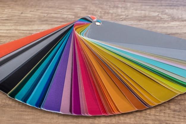 Próbnik w kolorowe paski do malowania na drewnianym biurku