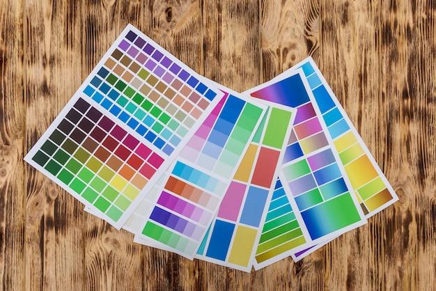 Próbniki papieru kolorowego na drewnianym stole.