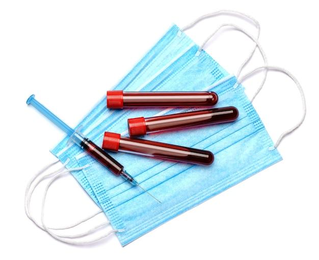 Probówka do badania krwi ze strzykawką, maska medyczna na białym tle, widok z góry.