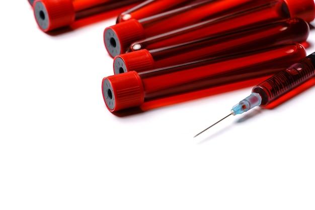 Probówki krwi z czerwoną wtyczką na białym tle.