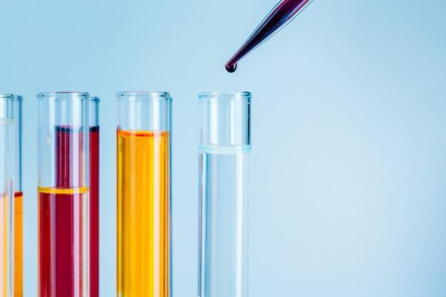Probówki laboratoryjne z czerwonymi i żółtymi płynami na jasnoniebieskim tle