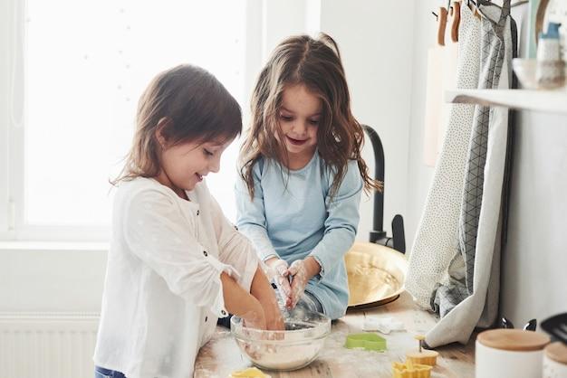 Próbując odtworzyć to, czego ich nauczono. przyjaciele z przedszkola uczą się gotować z mąki w białej kuchni.