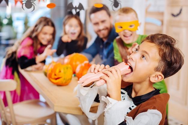 Próbuję ciasteczka. podekscytowany emocjonalny przystojny chłopak ubrany w jasny kostium na halloween, próbujący ręcznie ciastko