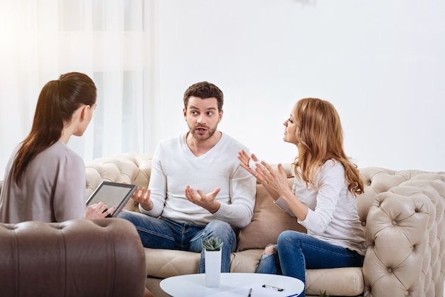 Próbuję pomóc. miła ciemnowłosa psycholog kobieta siedząca w fotelu i trzymając tablet podczas słuchania swojego pacjenta