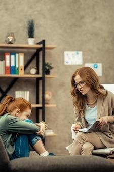 Próbuję pomóc. przyjemna, dobrze wyglądająca kobieta rozmawiająca z uroczą dziewczyną, próbując jej pomóc