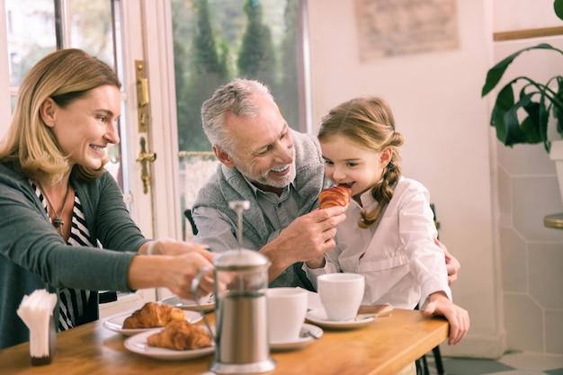 Próbuję rogalika. śliczna wnuczka z niezłą fryzurą próbuje pysznego rogalika jedzącego śniadanie z dziadkami