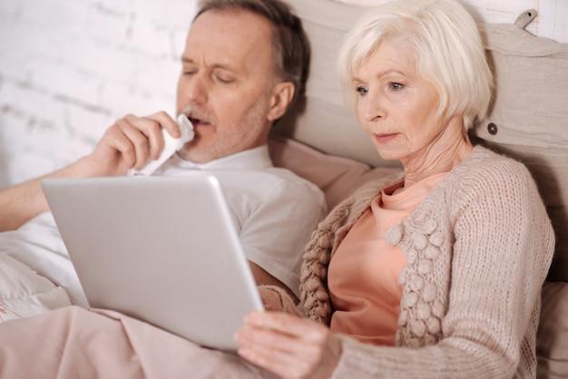 Próbuję się bawić. starsza kobieta, leżąc na łóżku obok kaszlącego męża i trzymając laptopa.