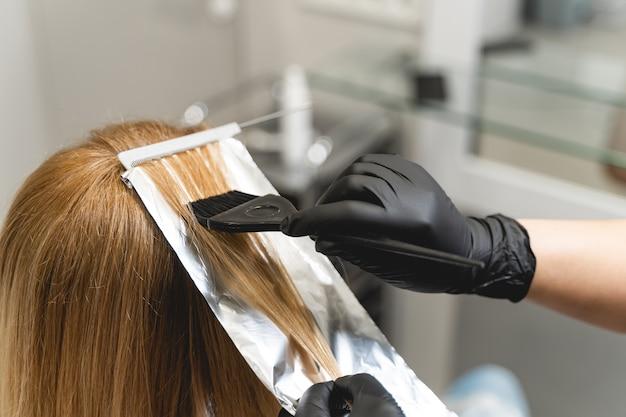 Procedura blond. profesjonalna osoba płci żeńskiej w sterylnych rękawiczkach podczas farbowania włosów dla swojego klienta. koncepcja piękna