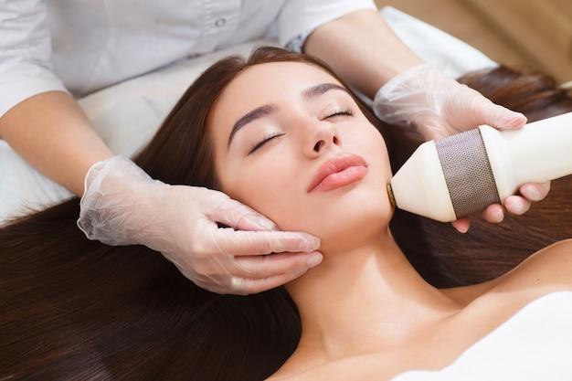 Procedura fotoepilacji w salonie kosmetycznym. kosmetologia sprzętowa. terapia mikroprądowa. ścieśniać
