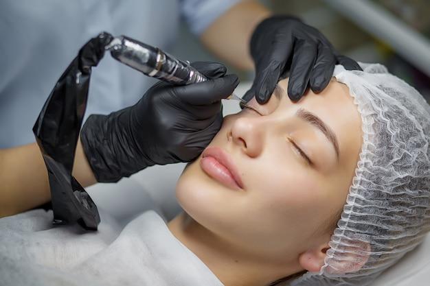 Procedura makijażu permanentnego eyeliner, nakładana na młodą dziewczynę