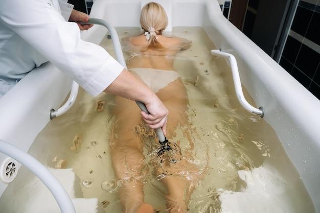 Procedura masażu podwodnego w łazience. dziewczyna o zabiegu masażu podwodnego.