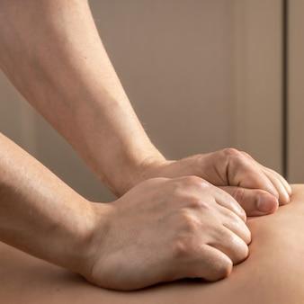 Procedura masażu, ręce masażysty wykonujące masaż pleców, koncepcja opieki zdrowotnej i urody