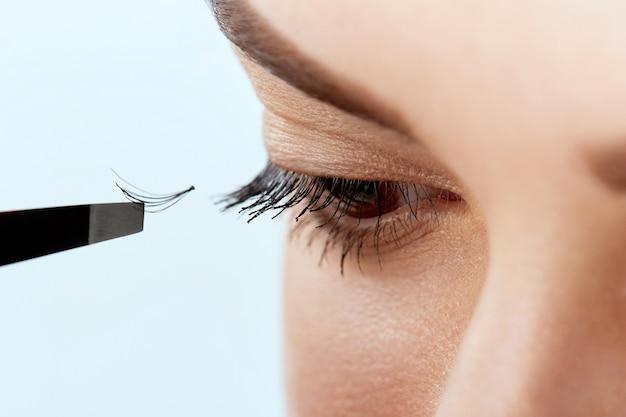 Procedura przedłużania rzęs. kobieta oko z długimi rzęsami. rzęsy, zbliżenie, makro, selektywne skupienie. kosmetyki i makijaż.