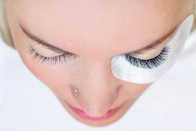 Procedura przedłużania rzęs. kobieta oko z długimi rzęsami. ścieśniać