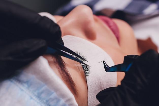 Procedura przedłużania rzęs. zamyka w górę widoku żeński oko z długimi rzęsami. stylista trzyma różowe pincety, szczypce i robi przedłużające się rzęsy. makro, selektywne ustawianie ostrości. pojęcie piękna. leczenie.