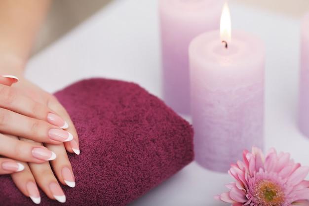Procedura spa, kobieta w salonie piękności trzymając palce w kąpieli aromatycznej na dłonie