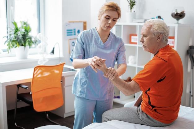 Procedura terapeutyczna. miła profesjonalna pielęgniarka stojąca obok pacjenta podczas masowania jego palców