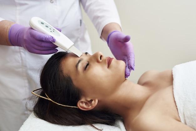 Procedura ultradźwiękowego czyszczenia twarzy. klinika kosmetologiczna
