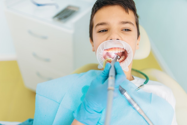 Procedura usuwania próchnicy, stomatologia dziecięca. kobieta dentysta wiercąca zęby, klinika stomatologiczna