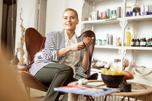 Procedura w salonie. spokojna piękna kobieta odpoczywa w strefie oczekiwania w studio kosmetycznym, stojąc z kosmetykiem z tyłu