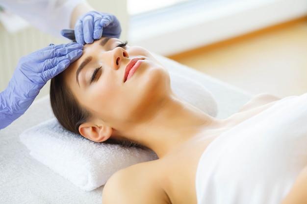 Procedury pielęgnacyjne skóry. piękna młoda kobieta w salonie spa. leżąc na stole do masażu i odpocznij. wysoka rozdzielczość