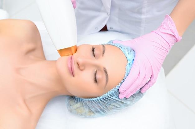 Procedury przeciwstarzeniowe. koncepcja pielęgnacji skóry. kobieta otrzymująca zabieg kosmetyczny twarzy, usuwanie pigmentacji w klinice kosmetycznej. intensywna terapia światłem pulsacyjnym. ipl. odmładzanie, fototerapia twarzy.