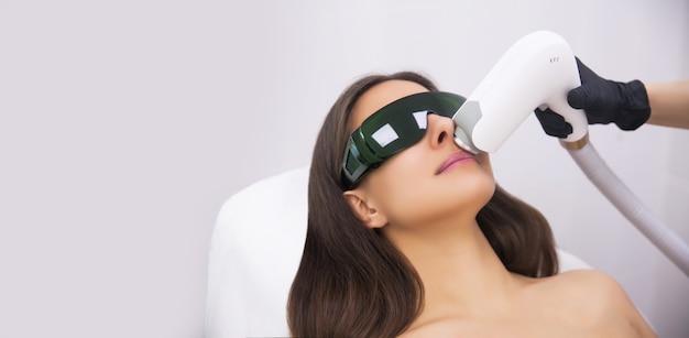 Procedury przeciwstarzeniowe. koncepcja pielęgnacji skóry. kobieta otrzymująca zabieg kosmetyczny twarzy, usuwanie pigmentacji w klinice kosmetycznej. intensywna terapia światłem pulsacyjnym. ipl. odmłodzenie, fototerapia twarzy.