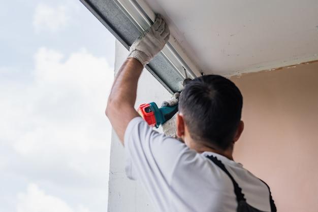 Proces człowieka za pomocą śrubokręta. pracownik dokonuje instalacji okna