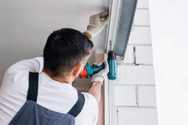Proces człowieka za pomocą śrubokręta. pracownik wykonuje instalację okna