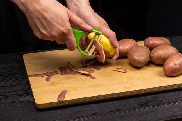 Proces czyszczenia ziemniaków specjalną obieraczką nożową. szef kuchni przygotowuje ziemniaki do smażenia lub gotowania.