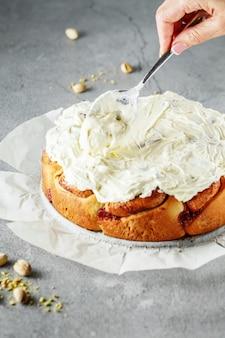Proces dekorowania ciasta kremem. ręce na zdjęciu
