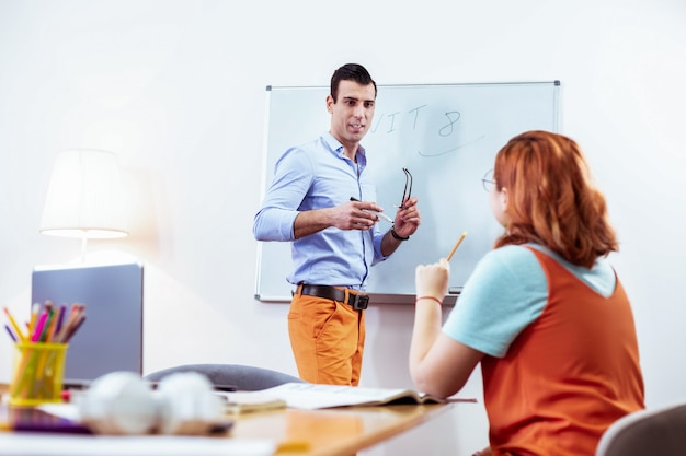 Proces edukacji. miła młoda kobieta patrząca na tablicę podczas zadawania pytań nauczycielowi