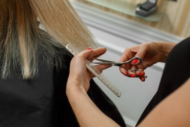 Proces fryzur. fryzjer z nożyczkami i grzebieniem w dłoniach. fryzjer obetnie końcówki zadbanych blond włosów. kursy dla fryzjerów.