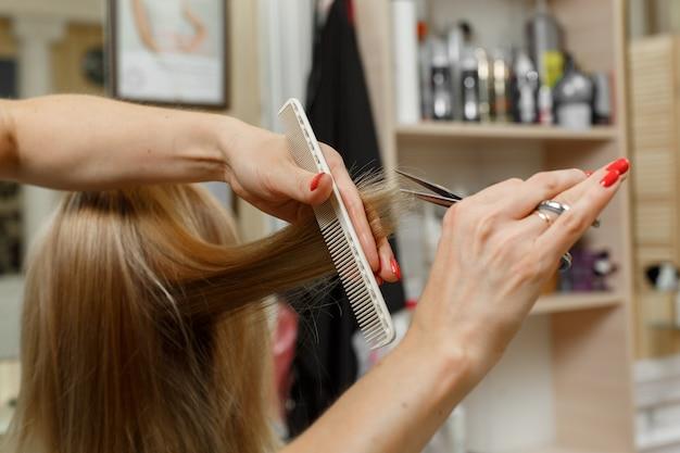 Proces fryzur. fryzjer z nożyczkami i grzebieniem w dłoniach. fryzjer obetnie końcówki zadbanych blond włosów. mistrz włosów