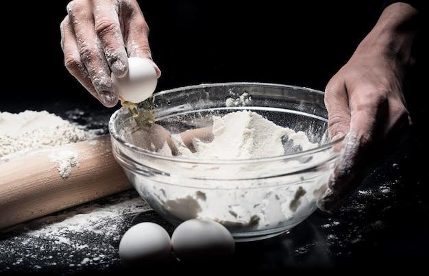 Proces gotowania. bliska mans ręce, wyrabiając ciasto i używając jaj i mąki podczas pracy w restauracji