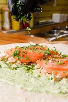 Proces gotowania burrito. kucharz dodaje warzywa do pomidorów i mięsa na pita z sosem. danie meksykańskie.