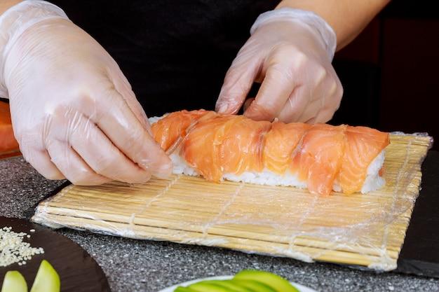 Proces gotowania japońskiej rolki sushi z łososiem.